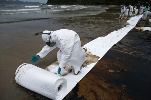 A Thai soldier rolls out a ream of special paper in a clean-up operation at Ao Prao Beach on Koh Samet
