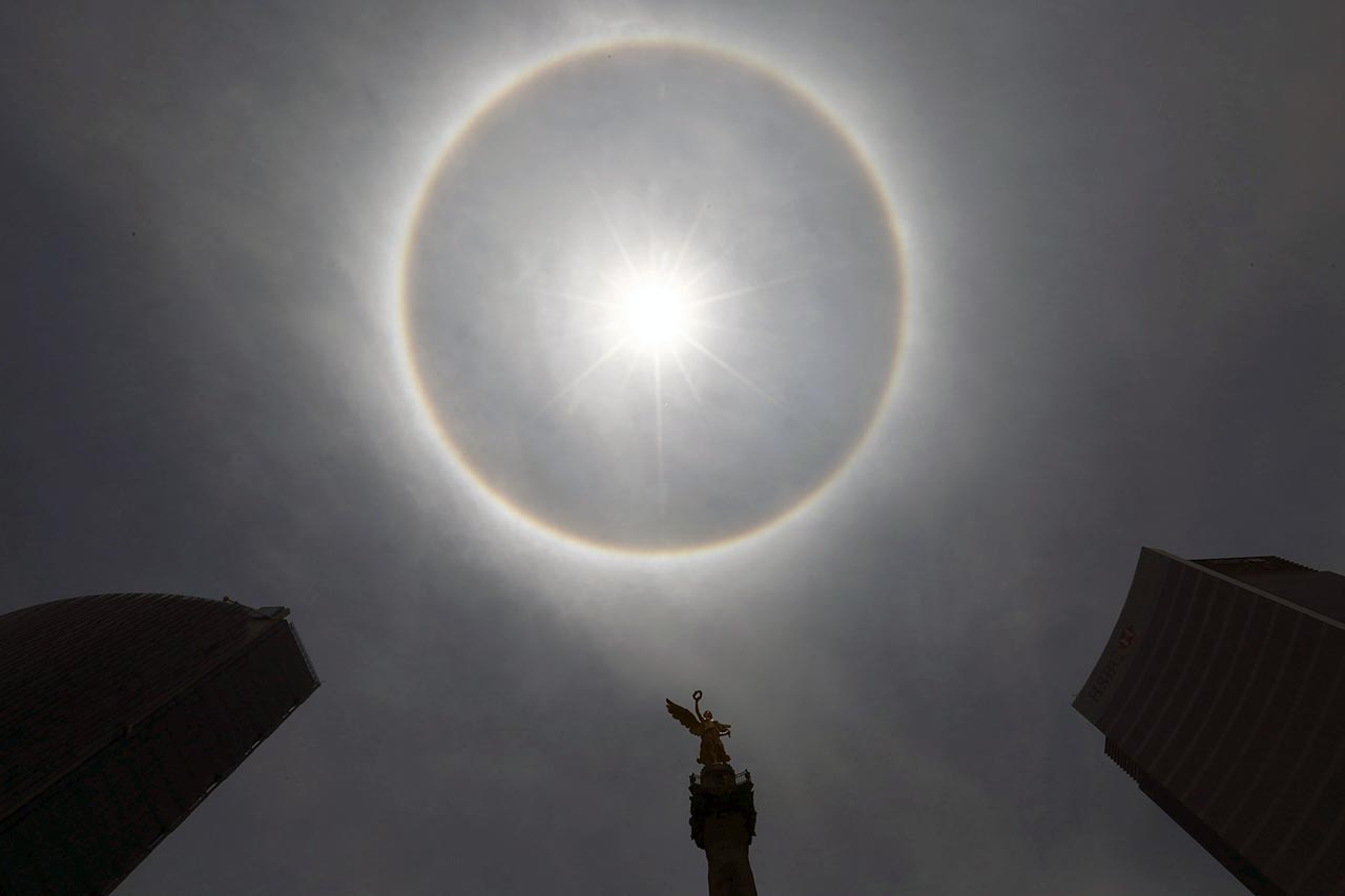 A view of a solar halo on Angel de la Independencia monument in Mexico City May 21, 2015. According to meteorologists, the weather phenomenon creates rainbows around the sun and is formed by the reflection of ice crystals. REUTERS/Edgard Garrido