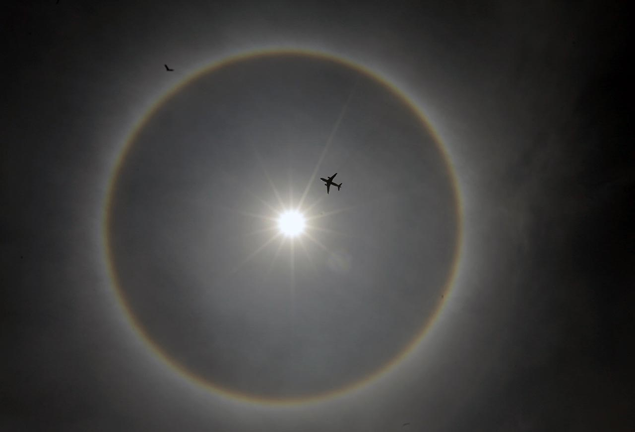 A plane flies past a solar halo in Mexico City May 21, 2015. According to meteorologists, the weather phenomenon creates rainbows around the sun and is formed by the reflection of ice crystals. REUTERS/Henry Romero
