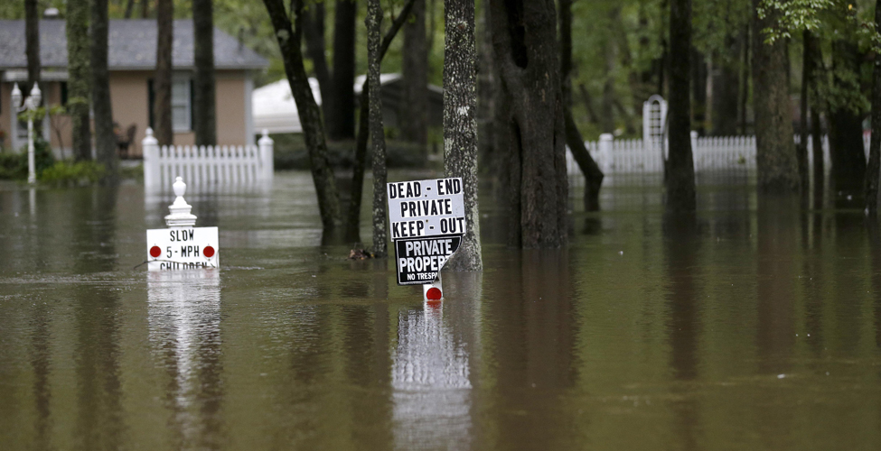 Floodwaters from nearby Black Creek swamp a neighborhood along East Black Creek Road in Florence, S.C., Monday, Oct. 5, 2015. Flooding continues throughout the state following record rainfall amounts over the last several days. (AP Photo/Gerry Broome)