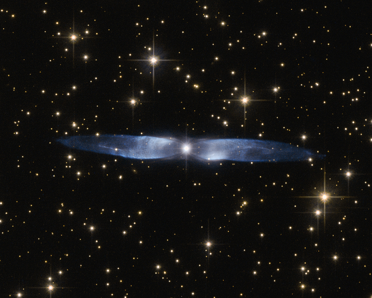 In this cosmic snapshot, the spectacularly symmetrical wings of Hen 2-437 show up in a magnificent icy blue hue. Hen 2-437 is a planetary nebula, one of around 3000 such objects known to reside within the Milky Way. Located within the faint northern constellation of Vulpecula (The Fox), Hen 2-437 was first identified in 1946 by Rudolph Minkowski, who later also discovered the famous and equally beautiful M2-9 (otherwise known as the Twin Jet Nebula). Hen 2-437 was added to a catalogue of planetary nebula over two decades later by astronomer and NASA astronaut Karl Gordon Henize. Planetary nebulae such as Hen 2-437 form when an aging low-mass star — such as the Sun — reaches the final stages of life. The star swells to become a red giant, before casting off its gaseous outer layers into space. The star itself then slowly shrinks to form a white dwarf, while the expelled gas is slowly compressed and pushed outwards by stellar winds. As shown by its remarkably beautiful appearance, Hen 2-437 is a bipolar nebula — the material ejected by the dying star has streamed out into space to create the two icy blue lobes pictured here.