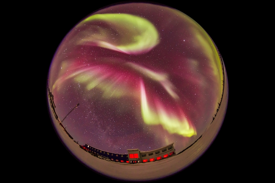 The great all-sky aurora display of March 6, 2016 over the Churchilll Northern Studies Centre, Churchill, Manitoba, in a view looking north. Here, the curtains have the characteristic green and red tint and converge to the zenith, with red dominating the sky at this point. This is one frame from a time-lapse sequence shot with the Sigma 8mm fish-eye lens and Canon 6D, intended for projection in digital planetarium theatres.