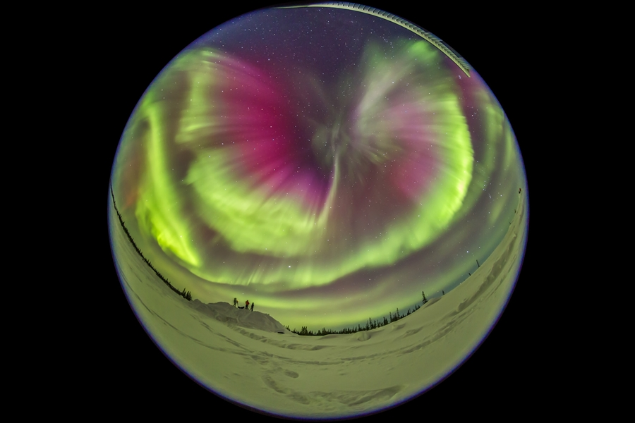 The great aurora of March 6, 2016 which lit up the entire sky in a dazzling display. Here, several of the staff and volunteers at the Churchill Northern Studies Centre gaze at and shoot the Northern Lights. The Big Dipper is at left. This is a frame from a time-lapse sequence taken with the Sigma 8mm fish-eye and Canon 6D, for projection in digital planetarium theatres.