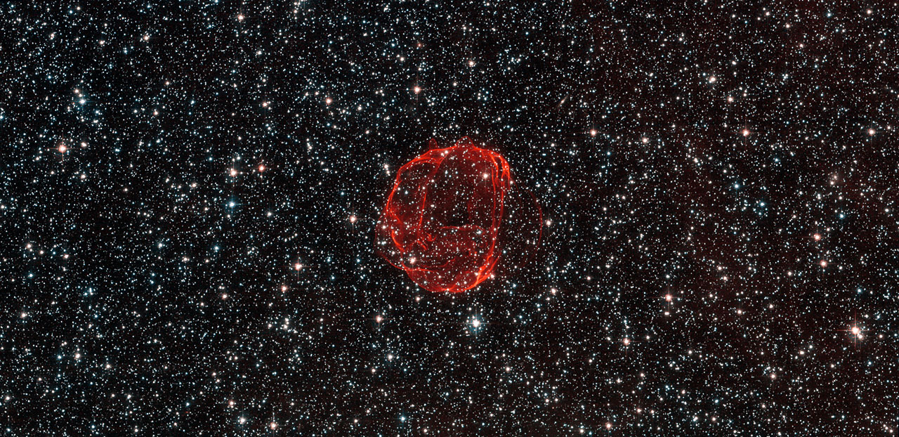 These delicate wisps of gas make up an object known as SNR B0519-69.0, or SNR 0519 for short. The thin, blood-red shells are actually the remnants from when an unstable progenitor star exploded violently as a supernova around 600 years ago. There are several types of supernova, but for SNR 0519 the star that exploded is known to have been a white dwarf star — a Sun-like star in the final stages of its life. SNR 0519 is located over 150 000 light-years from Earth in the southern constellation of Dorado (The Dolphinfish), a constellation that also contains most of our neighbouring galaxy the Large Magellanic Cloud (LMC). Because of this, this region of the sky is full of intriguing and beautiful deep sky objects. The LMC orbits the Milky Way galaxy as a satellite and is the fourth largest in our group of galaxies, the Local Group. SNR 0519 is not alone in the LMC; the NASA/ESA Hubble Space Telescope also came across a similar bauble a few years ago in SNR B0509-67.5, a supernova of the same type as SNR 0519 with a strikingly similar appearance. A version of this image was submitted to the Hubble's Hidden Treasures Image Processing Competition by Claude Cornen, and won sixth prize.
