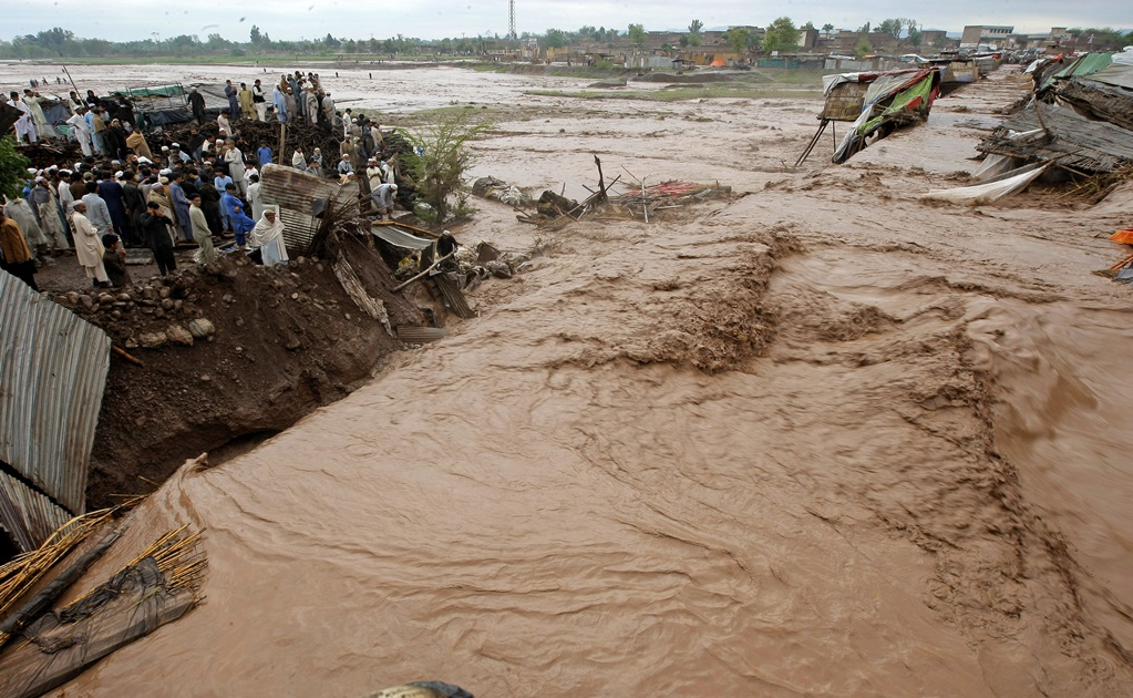 Pakistani villagers watch at flash flooding on the outskirts of Peshawar, Pakistan, Sunday, April 3, 2016. A Pakistani national disaster management official says flash floods triggered by torrential rains have killed dozens of  people in the country's northwest. (AP Photo/Mohammad Sajjad)