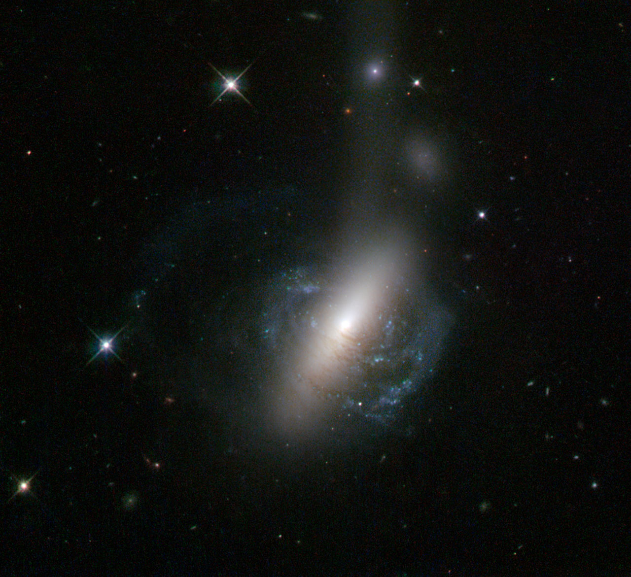 This  new image from the NASA/ESA Hubble Space Telescope captures an  ongoing cosmic collision between two galaxies — a spiral galaxy is in  the process of colliding with a lenticular galaxy. The collision looks  almost as if it is popping out of the screen in 3D, with parts of the  spiral arms clearly embracing the lenticular galaxy's bulge. The  image also reveals further evidence of the collision. There is a bright  stream of stars coming out from the merging galaxies, extending out  towards the right  of the image. The bright spot in the middle of the plume, known as ESO  576-69, is what makes this image unique. This spot is believed to be the  nucleus of the former spiral galaxy, which was ejected from the system  during the collision and is now being shredded by tidal forces to  produce the visible stellar stream. A version of this image was entered into the Hubble's Hidden Treasures image processing competition by contestant Luca Limatola.