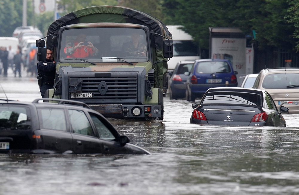 A police officers hangs on a military vehicle on its way through the flooded suburb of Villeneuve-Trillage in Villeneuve Saint-Georges, outside Paris, June 3, 2016 after days of almost non-stop rain caused flooding in the country. REUTERS/Christian Hartmann