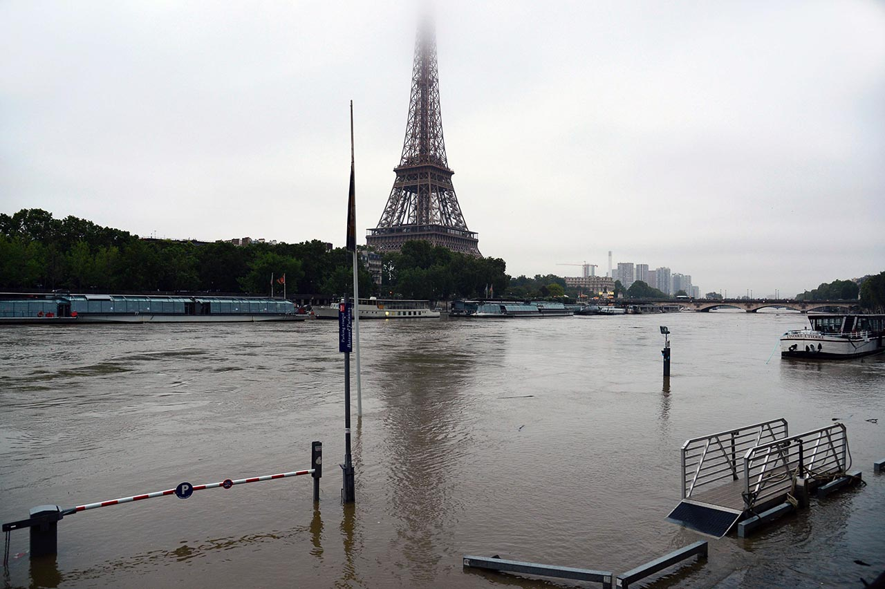 TOPSHOT - A photo taken on June 1, 2016 shows the Eiffel Tower facing the flooded Seine river in Paris. Four bodies were found floating in homes in France and Germany on June 1, 2016  in flash floods that left water lapping at the doors of one of the Loire Valley's most famous chateaux. Heavy rains lashing parts of France, Germany and Austria cut roads, stranded people on rooftops and forced schools to close their doors, and French weather forecasters warned of more to come on June 2.  / AFP PHOTO / BERTRAND GUAY