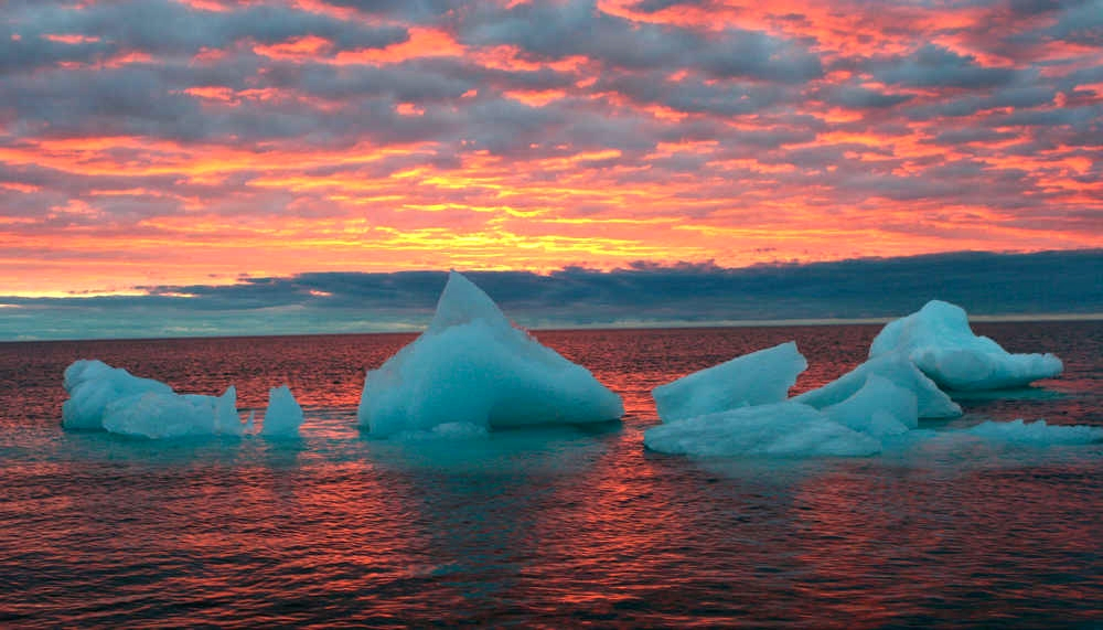 FILE - In this Sept. 13, 2006 file photo, ice chunks float in the Arctic Ocean as the sun sets near Barrow, Alaska. For the first time since May, the sun has set in what is billed as the northernmost city in the United States. According to the National Weather Service, the first sunset in Barrow, Alaska, since May 10 occurred at 1:57 a.m. Friday. Barrow has continuous daylight for so long because of its location and the tilt of the earth's axis. (AP Photo/Arctic Sounder, Beth Ipsen)