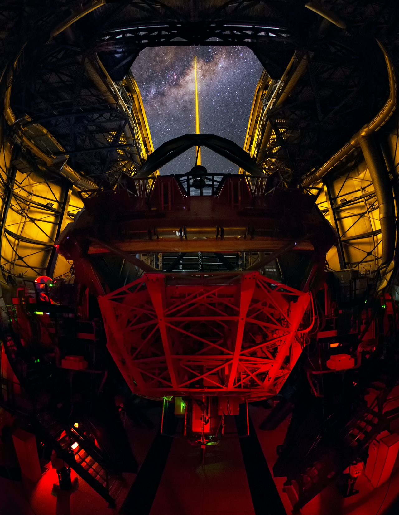 Taken from inside the dome of the fourth Unit Telescope of ESO's Very Large Telescope (VLT), this spectacular shot from ESO Photo Ambassador Yuri Beletsky captures the VLT's Laser Guide Star (LGS) in action. The LGS, located on top of the 1.2-metre secondary mirror of Unit Telescope 4, is part of the VLT's adaptive optics system. By creating a glowing spot — an artificial star — in the Earth's atmosphere at an altitude of 90 kilometres, the light coming back from the laser can be used as a reference to remove the effects of atmospheric distortion. This allows the telescope to produce astronomical images almost as sharp as if the telescope were in space. The plane of the Milky Way, seemingly pierced by the laser as it soars above the open dome of the telescope, is rippled with dark clouds of interstellar dust that block visible light. However, thanks to the telescope's infrared instruments and the adaptive optics system, astronomers can study and image our galaxy's complex and turbulent core in unprecedented detail.