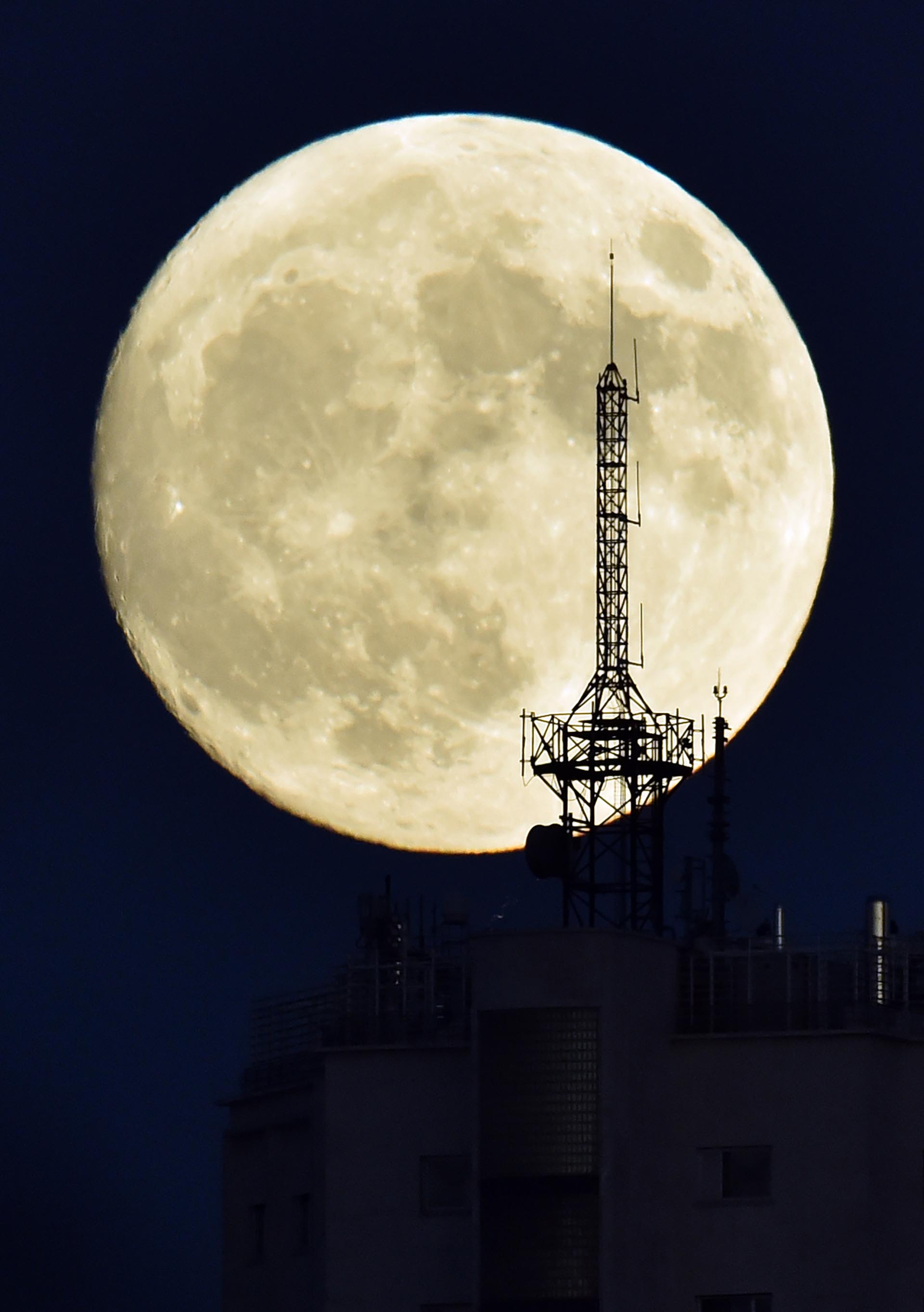 """The moon rises over an antenna on the top of a building in Madrid on November 13, 2016, on the eve of a """"supermoon"""". On November 14, 2016, the moon will orbit closer to the earth than at any time since 1948, named a 'supermoon', it is defined by a Full or New moon coinciding with the moon's closest approach to the Earth. / AFP PHOTO / GERARD JULIEN"""