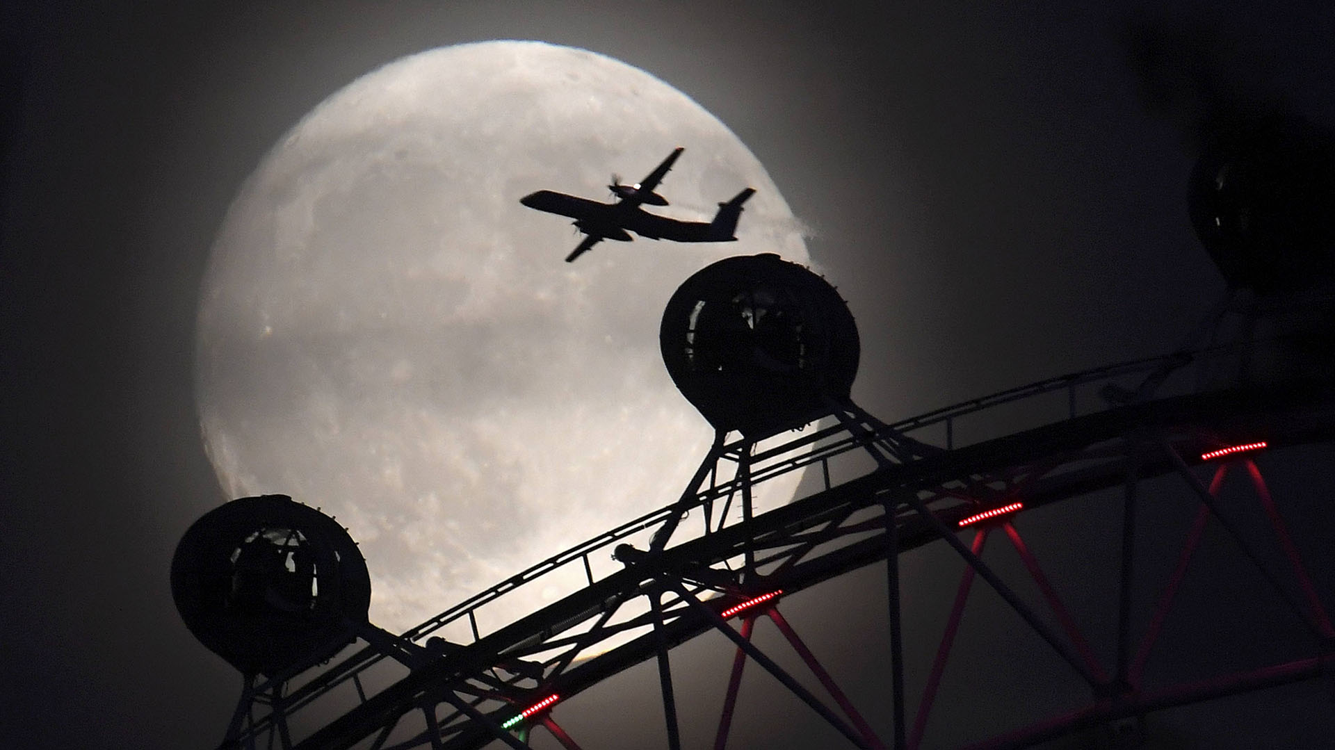 """An aeroplane flies past the London Eye wheel, and moon, a day before the """"supermoon"""" spectacle in London, Britain, November 13, 2016. REUTERS/Toby Melville"""