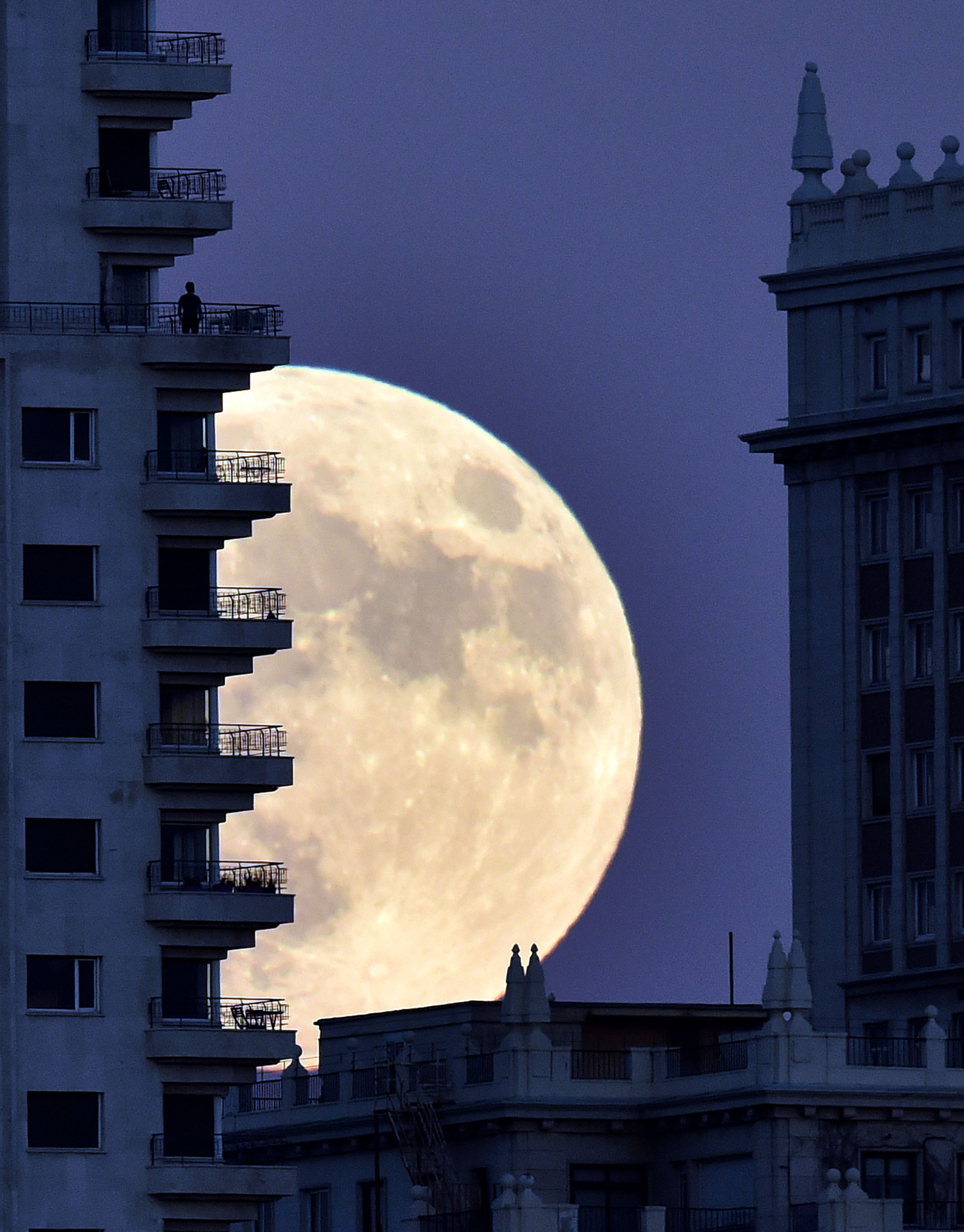 """A man stands on a balcony of a building of Madrid as the moon rises in background, on November 13, 2016, on the eve of a """"supermoon"""". On November 14, 2016, the moon will orbit closer to the earth than at any time since 1948, named a 'supermoon', it is defined by a Full or New moon coinciding with the moon's closest approach to the Earth. / AFP PHOTO / GERARD JULIEN"""